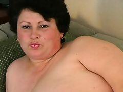 Зрелая толстая мама расслабляется на диване