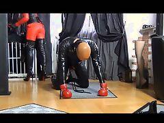 Зрелая повелительница в латексе наказывает раба на полу