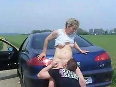 Молодой водитель вылизывает стареющую шлюху на багажнике на дороге