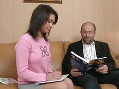Молодая студетка выполняет работу над ошибками у старого преподавателя дома